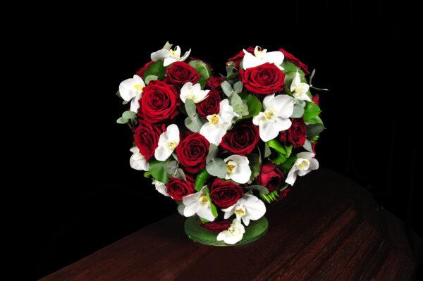 Afscheidsbloemen hart witte orchideeën rode rozen (foto grafkist)