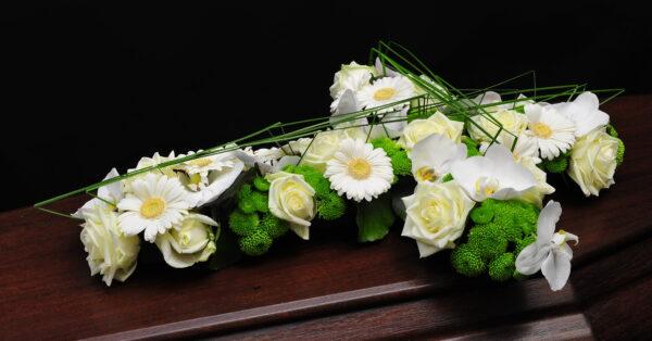 Afscheidsbloemen modern bloemstuk kruisvorm (foto grafkist)