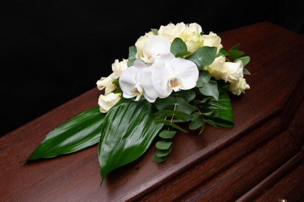 Afscheidsbloemen orchideeën kistversiering wit (foto grafkist)